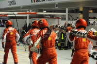 Ferrari mechanics on their way back to the pit box, fuel hose included