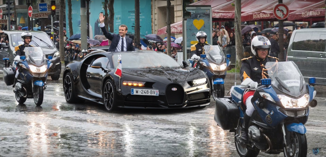 french president emmanuel macron greets people from bugatti chiron