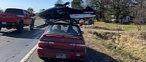If It Fits, It Ships: Toyota Corolla Hauls Snowmobile on the Roof