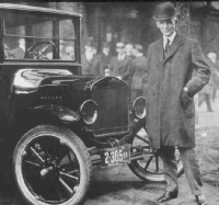 Henry Ford standing by his Model T