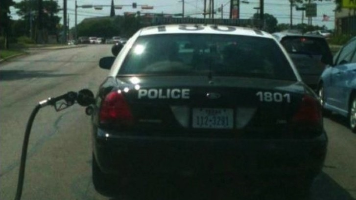 Police Car Driving with Gas Pump Nozzle: Real Photo