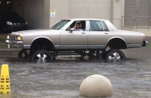 Jacked Up Car Driving Through Flood