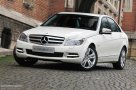 Mercedes Benz C 200 three quarters front view, lights on